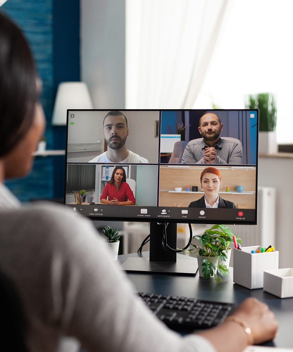 An image of an African American in a teleconference with multiple other people.